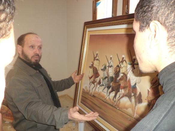 فنان لقيناه بالمعرض يحدثنا عن إحدى لوحاته الفنية